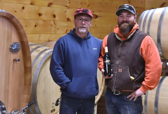 Ralph Stabile, 55,  left, and son Dustin Stabile, 34, co-owners of Mackinaw Trail Winery in Petoskey, are seen in the barrel room Wednesday, Oct. 30, with a bottle of their signature Marquette red wine.  Photography by John L. Russell