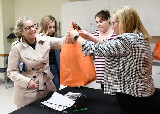 With her daughter, Grace Novak, 20, Chrissy Novak, 53, left, of Royal Oak picks up a water filter from Oakland County health officer Leigh-Anne Stafford, right, at the Leo Mahany/Harold Meininger Senior Community Center.