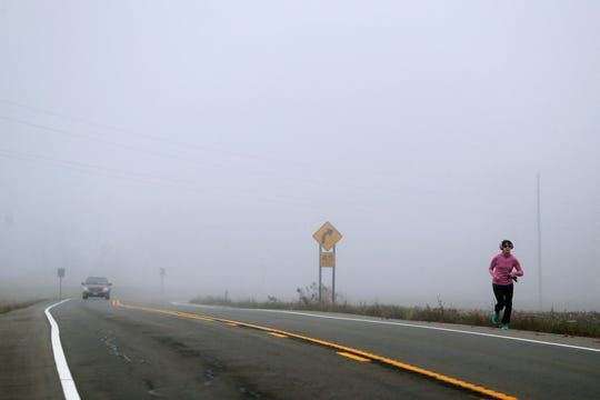Fog blankets Route 34 as a woman runs on the road's shoulder during a morning jog in Lansing, N.Y. A