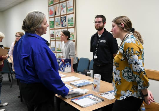 Health education intern Caitlyn Toth, right, and public health educator Daniel McIntyre talk with Royal Oak resident Gretchen Smith, left, while distributing information about lead exposure at the Leo Mahany/Harold Meininger Senior Community Center in Royal Oak.