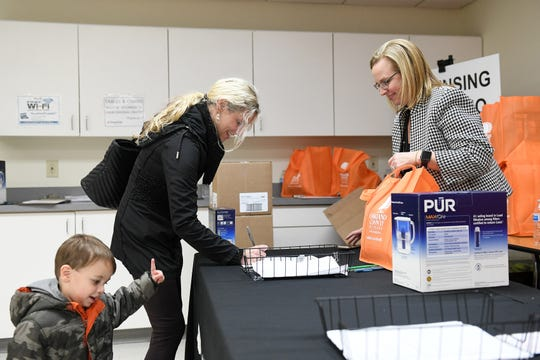 With her son, Sterling Ashton, 2, Gina Ashton, 36, of Royal Oak signs up for a water filter pitcher with Oakland County health officer Leigh-Anne Stafford, right, at the Leo Mahany/Harold Meininger Senior Community Center in Royal Oak.