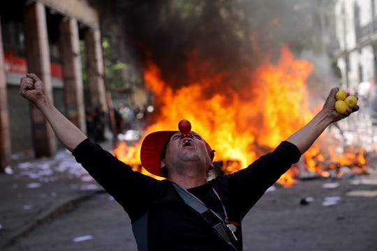 An anti-government demonstrator screams in font of a burning barricade in Santiago, Chile, Tuesday, Oct. 22, 2019. Protests in the country have spilled over into a fifth day, even after President Sebastian Pinera cancelled the subway fare hike that prompted rioting, arson and violent clashes that have almost paralyzed the country.