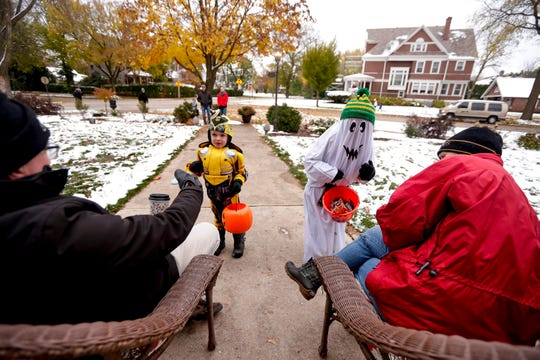Al and Sally Hicks pass out candy to Luke and Jack Everman, right, during trick-or-treating on Thursday near Astor House in Green Bay.