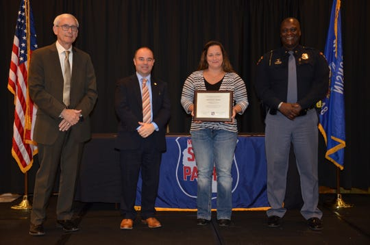 Carmen McVane, a civilian who helped save a crash victim's life, accepts her Lifesaving Award at the 2019 Wisconsin State Patrol Awards.