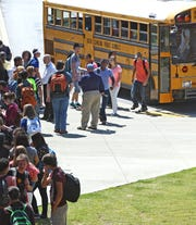 D.W. Daniel High School students return from the career campus and others wait to get on the bus after the first day of school for Pickens County.