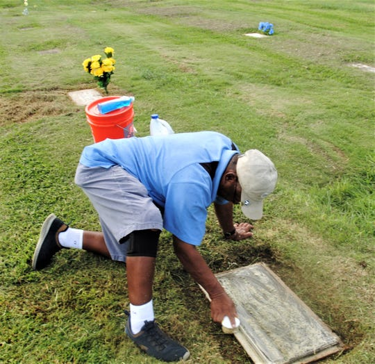 John Salas of Chalan Pago cleans his father and mother's graves on Oct. 31 in preparation for for All Souls' Day.