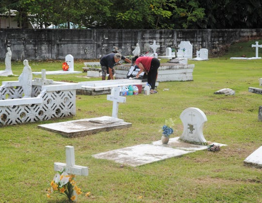 Dan and Lou Sablan of Dededo were cleaning up the grave of a former boss's relative at the Pigo Catholic Cemetery in Hagåtña Oct. 31 in preparation for All Souls' Day.