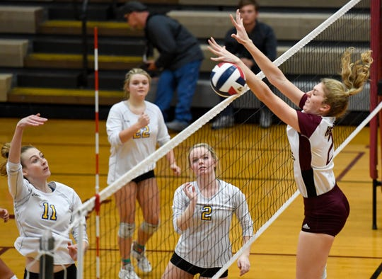 Henderson's Brooke Springer (2) jumps to block a shot from Caldwell County's Abby Griggs (11) at the net as the Henderson County Lady Colonels play the Caldwell County Lady Tigers in the semifinals of the Second Region volleyball tournament at Madisonville-North Hopkins High School Wednesday evening, October 30, 2019.