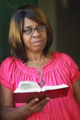 Rosa Campbell stands with her Bible at her Indianapolis home on Aug. 23, 2013.  She often reads the Bible to combat the demons possessing her daughter and grandchildren.