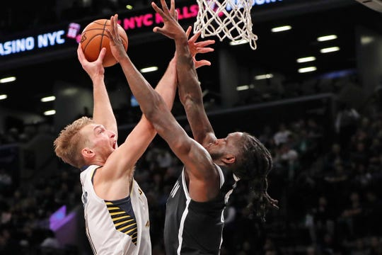 Brooklyn Nets forward Taurean Prince, right, defends against Indiana Pacers forward Domantas Sabonis as Sabonins goes up for a layup during the first half of an NBA basketball game Wednesday, Oct. 30, 2019, in New York.