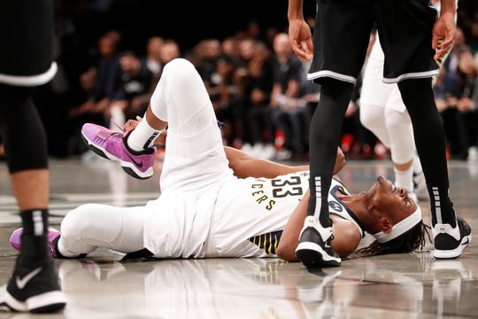 Indiana Pacers center Myles Turner (33) grabs his ankle after falling to the floor during the first half of the team's NBA basketball game against the Brooklyn Nets, Wednesday, Oct. 30, 2019, in New York. After the injury, Turner left the court with help from a trainer and team staff.