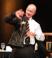 Indiana Gov. Mitch Daniels slips on a leather Harley-Davidson motorcycle jacket with the Purdue emblem on it, given to him by the university's Board of Trustees.