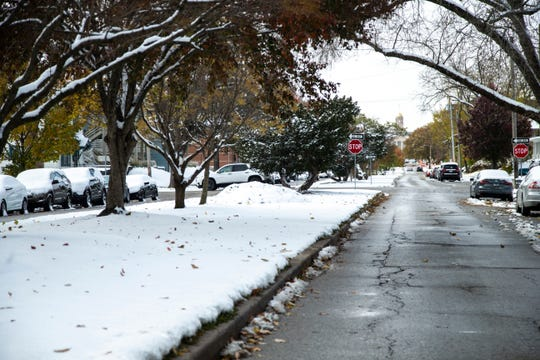 Snow covers the ground while trees lose their leaves on the morning of Halloween, Thursday, Oct., 31, 2019, along Iowa Avenue towards the Old Capitol in Iowa City, Iowa.