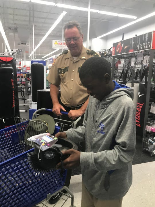 Tennessee Highway Patrol Officer Brad Wilbanks helps a student pick out a skateboard helmet at Academy Sports and Outdoors in Jackson on Oct. 28, 2019.