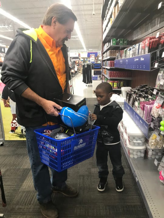 After getting a soccer ball and football, one student from the Boys and Girls Club picks out a set of golf balls to bring home as well, at Academy Sports and Outdoors in Jackson on Oct. 28, 2019.
