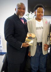 Charleston Terrance Neal Jr., 19, stands with Pastor Ricky Carter at a book-signing Oct. 27 at Good Hope Baptist Church in Lafayette.