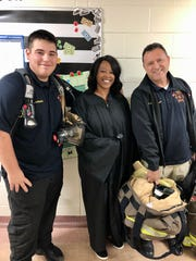 Scott firefighters Edward Cazares and Hayden Gannard stand with Westside Elementary counselor Monica Scranton dressed as a judge for Career Day Thursday, Oct. 31.