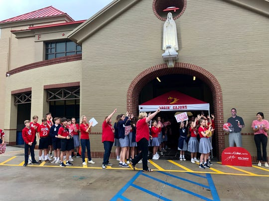 "Our Lady of Fatima Catholic School faculty and students cheer for judges for the ""Paint the Town Red"" competition for UL Homecoming Week."