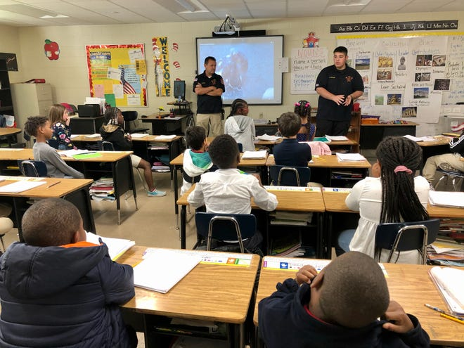 Scott firefighters Edward Cazares and Hayden Gannard speak to students at Westside Elementary for Career Day Thursday, Oct. 31.