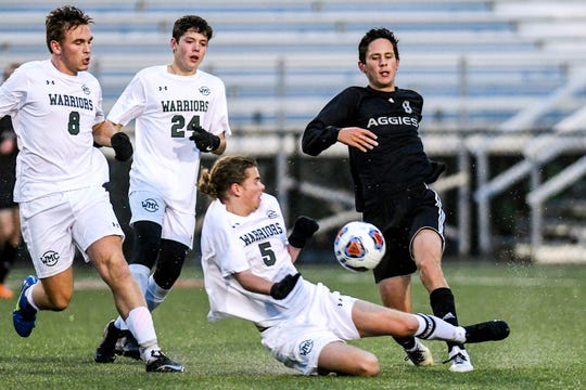Dansville's Cody Luce, right, kicks the ball as Western Michigan Christian's Charlie Alfree slides in during the first half on Wednesday, Oct. 30, 2019, at the Pat Patterson Athletic Field in Kentwood. Alfree's teammates, from left, Nick Moser and Ashton Leffring look on.