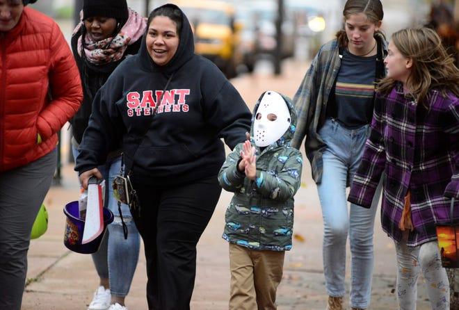Isaiah Bryan, 5, rubs his hands together during a blustery, cold Thursday on North Main Street during the Downtown Mansfield Business trick-or-treat. There were gusts of wind as high as 32 mph.