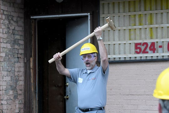 Renaissance Performing Arts Association CEO Mike Miller celebrates after ceremonial swing with a sledgehammer on the Rainbow Mortgage building Wednesday afternoon.