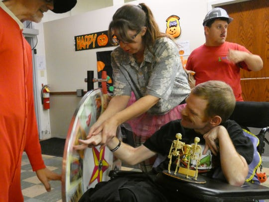 A staff member at MARCA Industries helps Andy Miller spin the wheel at MARCA's Halloween party last fall. MARCA has been forced to shutter its adult day care over concerns of the spread of coronavirus.