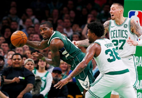 Bucks guard Eric Bledsoe looks to make a past as he is guarded by the Celtics' Marcus Smart and Daniel Theis.