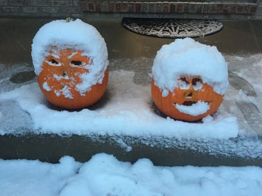 Jack-o'-lanterns are shown with a healthy coating of snow on a front porch in Germantown early Thursday.