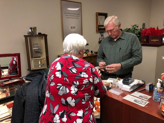 David Krumenacher helps a customer with her jewelry.