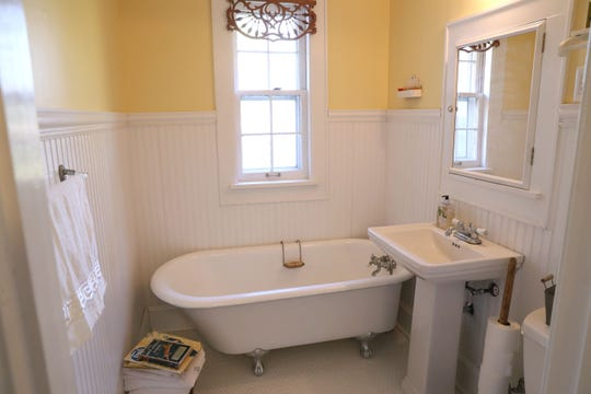 The claw-foot tub in the first-floor bathroom was blue; the homeowner painted it white.