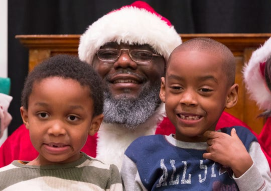 Making his annual appearance as Santa, Robert Boyd poses for a photo with Ayden Harris (left), 4, and Jaron Thornton, 5, Tuesday, December 25, 2018 at the Wisconsin Center.