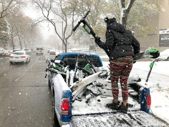 A woman, who didn't want to give her name, loads snow-covered Lime electric scooters into her truck Oct. 31 on North Prospect Avenue in Milwaukee.