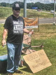 Homeless advocate Patrick Aitkens protests the panhandling ordinance