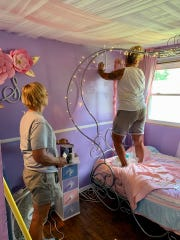 Dina Byrnes and Lynne Hatfield work on setting up Sarah's princess carriage bed.