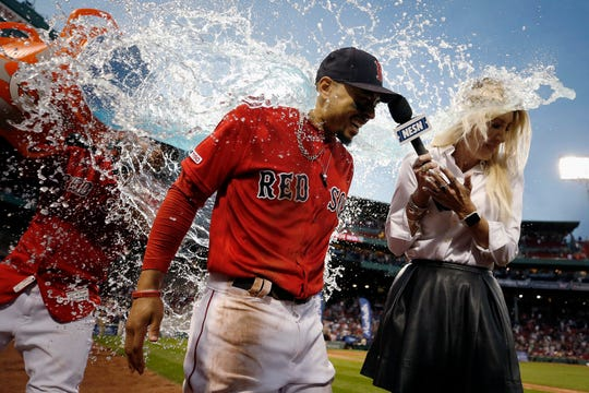 A teammate douses Boston Red Sox's Mookie Betts, who scored a walkoff run during the ninth inning against the Baltimore Orioles on Sept. 29, 2019.
