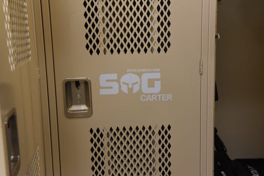 Newark Police Officer Adam Carter's locker displays a sticker for the division's Special Operations Group.