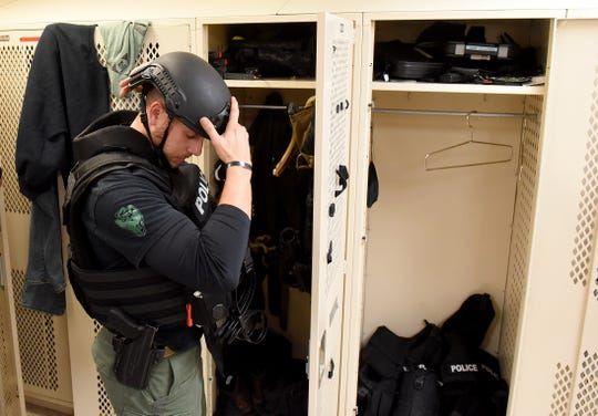 Newark Police Officer Ryan Fumi puts on his gear for a demonstration for the Citizens' Police Academy on Wednesday, Oct. 30, 2019. Fumi is part of the Newark Division of Police Special Operations Group, which turned 30 this year in January.