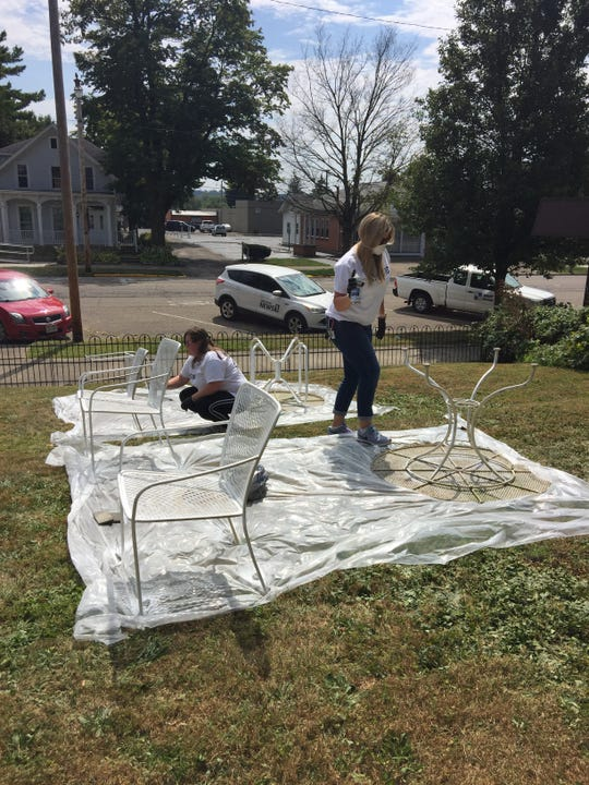 MedBen employees help spruce up furniture to be used by the Carol Strawn Center, which operates and adult day care for people with Alzheimer's and related disorders.
