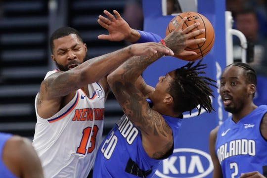 New York Knicks' Marcus Morris, left, fouls Orlando Magic's Markelle Fultz as he goes up for a shot during the first half of an NBA basketball game, Wednesday, Oct. 30, 2019, in Orlando, Fla. (AP Photo/John Raoux)