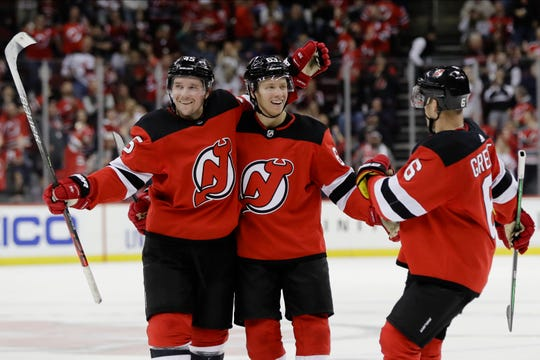 New Jersey Devils' Sami Vatanen (45) and Andy Greene (6) celebrate with Jesper Bratt after Bratt scored a goal during the second period of an NHL hockey game against the Tampa Bay Lightning on Wednesday, Oct. 30, 2019, in Newark, N.J.