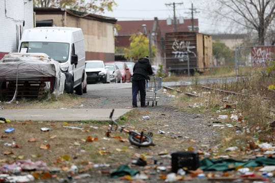 A person pushes a shopping cart along the abandon train tracks, towards Wall St. in Passaic. Wednesday, October 30, 2019