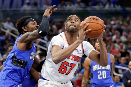 New York Knicks' Taj Gibson (67) looks for a shot against Orlando Magic's Terrence Ross, left, during the first half of an NBA basketball game, Wednesday, Oct. 30, 2019, in Orlando, Fla. (AP Photo/John Raoux)