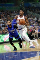 New York Knicks' RJ Barrett, right, drives around Orlando Magic's D.J. Augustin (14) during the first half of an NBA basketball game, Wednesday, Oct. 30, 2019, in Orlando, Fla. (AP Photo/John Raoux)
