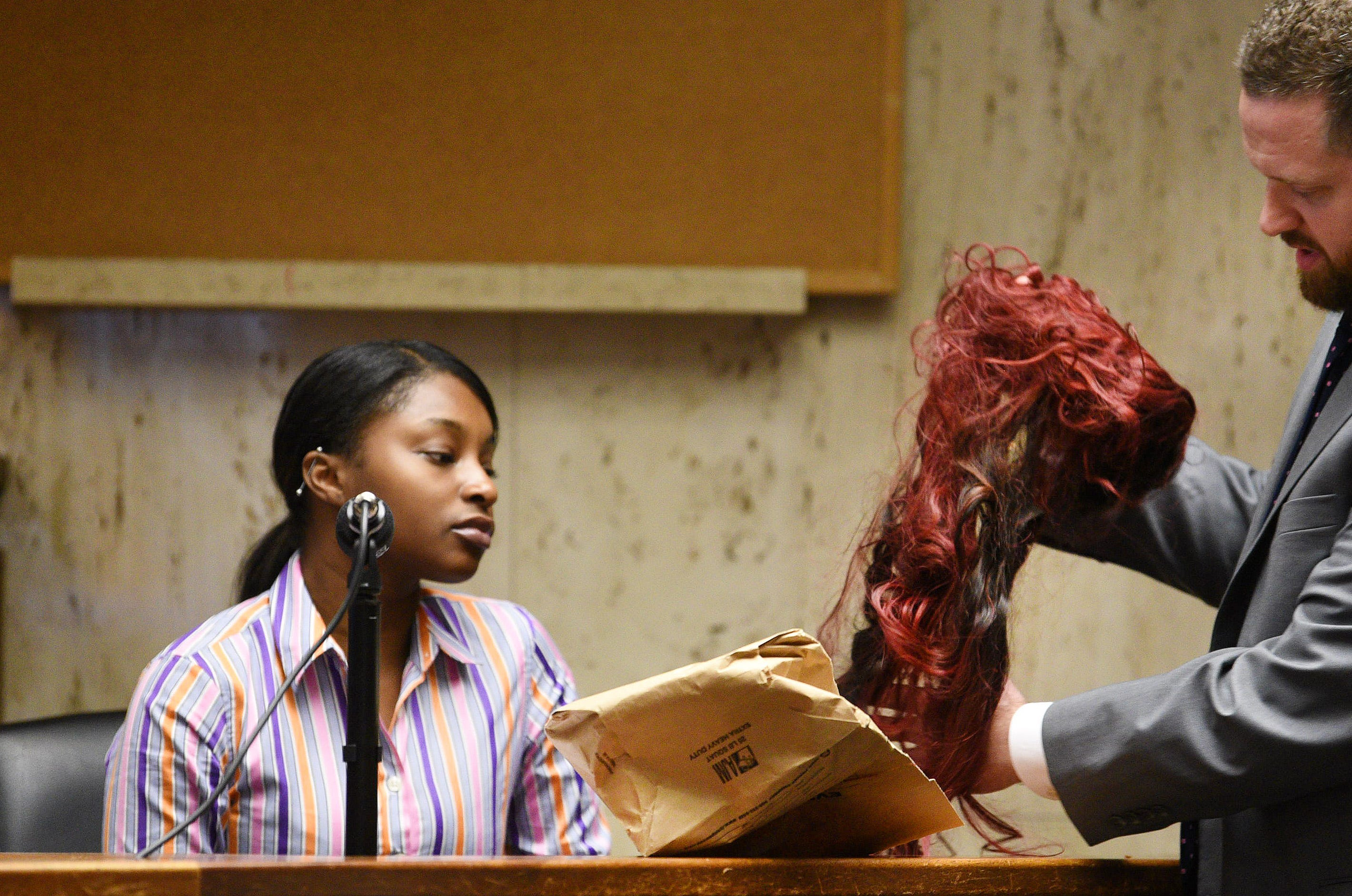 LaMia Brown looks at a hair extension worn by Sarah Butler on during Khalil Wheeler-Weaver's trial in Essex County Court on Oct. 31, 2019.