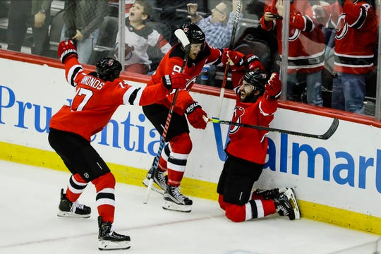 New Jersey Devils' Kyle Palmieri (21) celebrates with Taylor Hall (9) and Wayne Simmonds (17) after scoring his third goal, during the third period of the team's NHL hockey game against the Tampa Bay Lightning on Wednesday, Oct. 30, 2019, in Newark, N.J. The Lightning won 7-6.