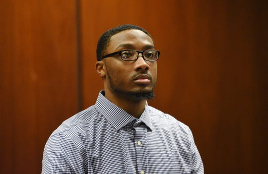 Khalil Wheeler-Weaver, 23, who is charged in the deaths of three women in 2016, stands as the jury enters the court room in Essex County Superior Court.