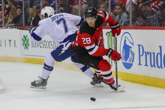 Devils' Damon Severson works his way around Mathieu Joseph during the first period Wednesday, Oct. 30, 2019 at Prudential Center in Newark.