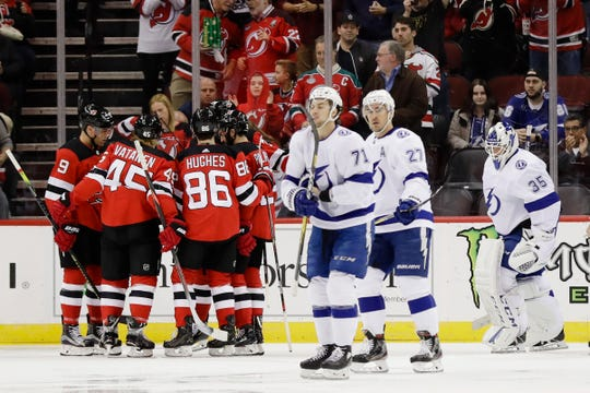 Tampa Bay Lightning goaltender Curtis McElhinney (35), Ryan McDonagh (27) and Anthony Cirelli (71) react as the New Jersey Devils celebrate a goal by Kyle Palmieri during the first period of an NHL hockey game Wednesday, Oct. 30, 2019, in Newark, N.J.