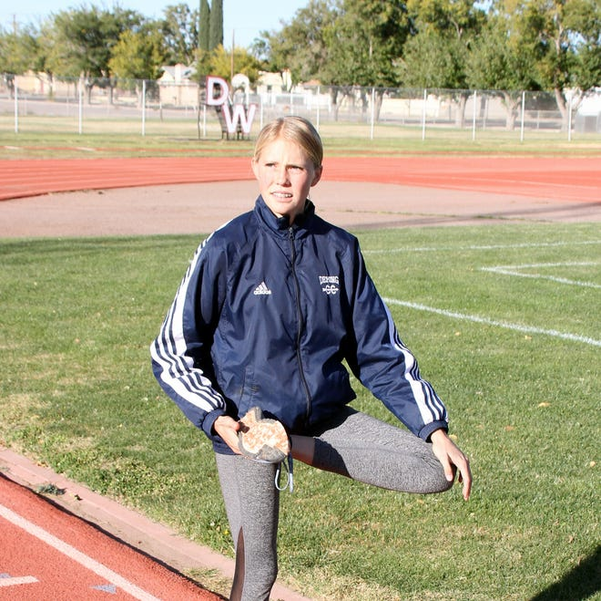 Sophomore Lady 'Cat cross country runner Lexi Walker goes through some stretching exercises prior to Wednesday's team practice at DHS Memorial Stadium.